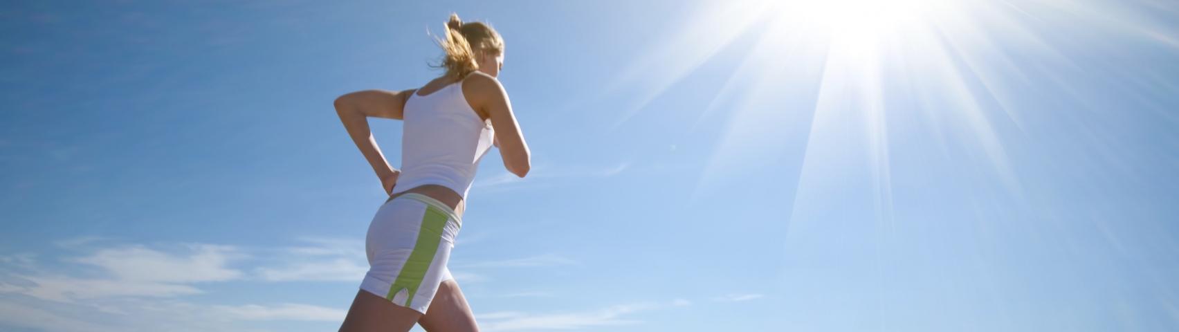 Women running on beach in sunshine