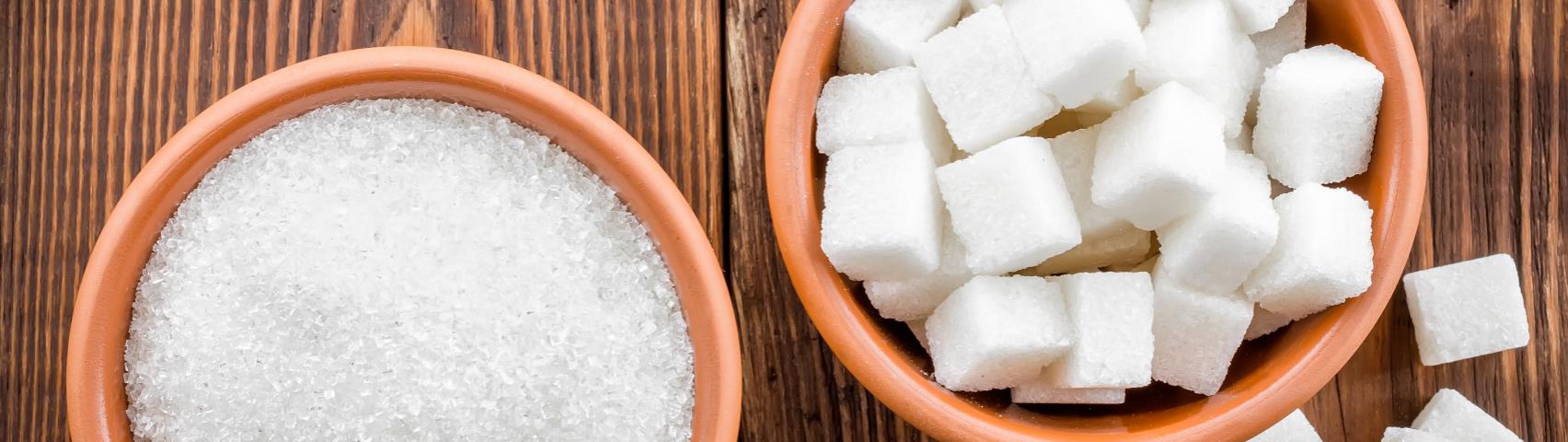 one bowl of sugar granules, one of sugar cubes