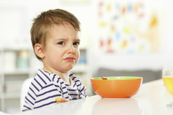 Unhappy young child eating breakfast