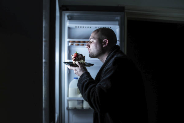 Man snacking from fridge at nighttime