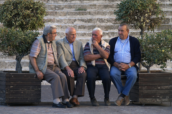 Four elderly men sitting on a bench