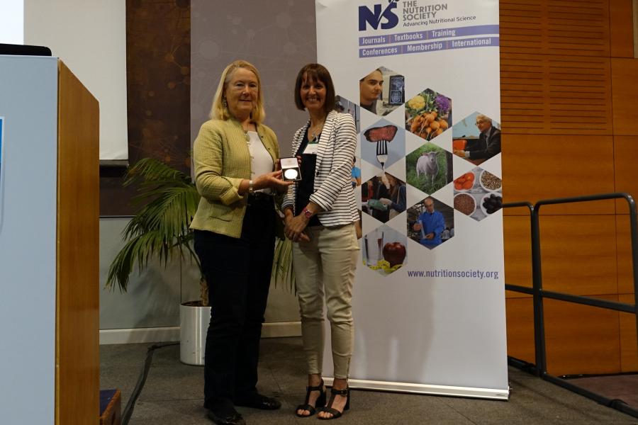 Dr Charlotte Evans receives the Medal from past President, Professor Catherine Geissler