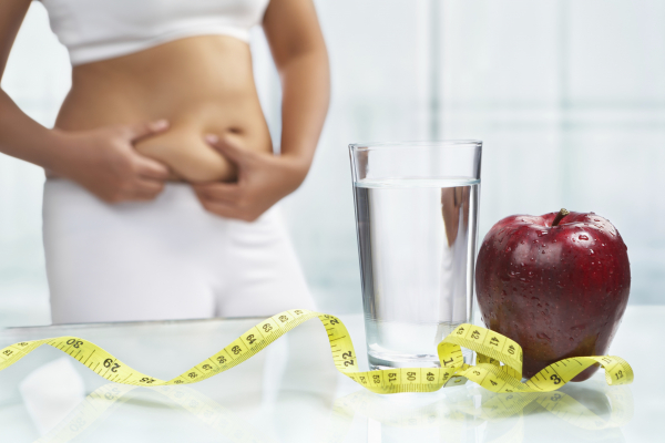 Women pinching waist behind a glass of water, apple and tap measure