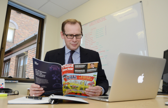 CEO, Mark Hollingsworth in his office reading a magazine