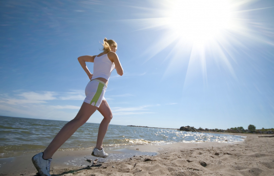 Women running on beach in sunshine