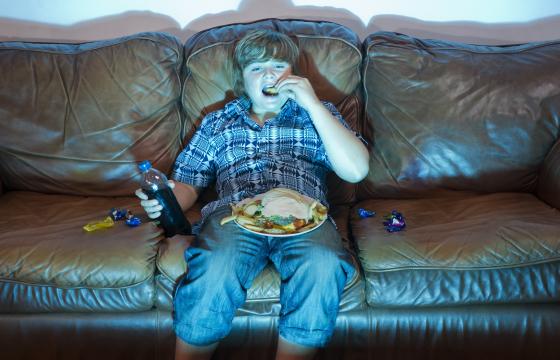 Boy watching TV eating dinner