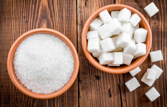 one bowl of sugar granules, one of sugar cubes