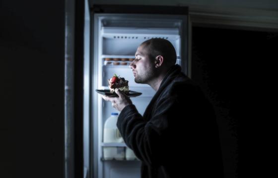 Man snacking from fridge at nighttime