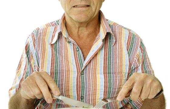 Elderly man eating lettuce